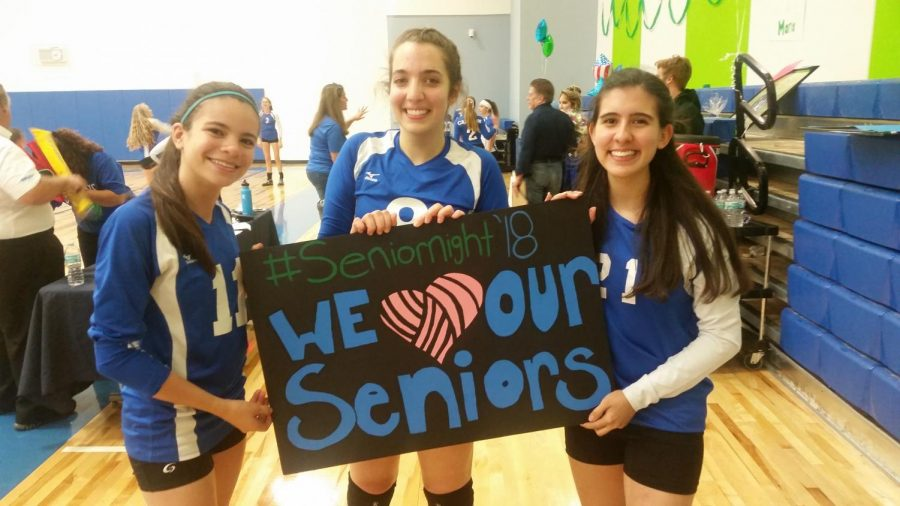 Seniors Maria Werden, Misha Dilmaghani, and Christina Rodriguez hold a fan's sign.