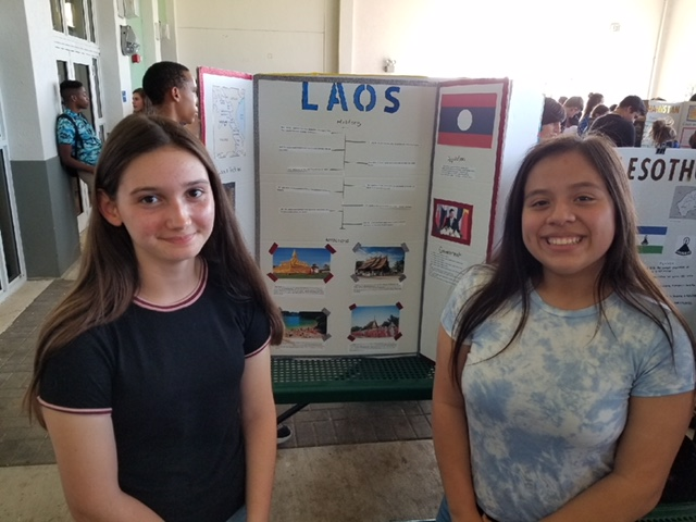 Two+students+stand+beside+their+Laos+poster+board.