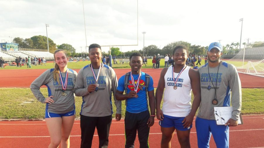(Left to right) Cara Salsberry, Tre'main Robinson, Jobed Phanord, Giordani Point Du Jour, and Coach Rhoden smile for the camera as the athletes display their well-earned medals.