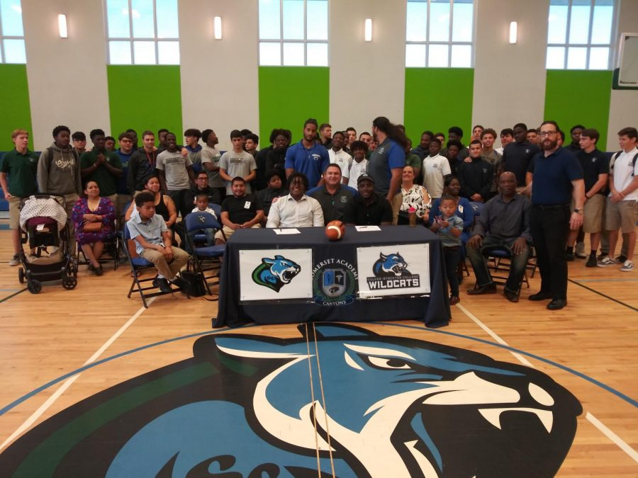 Devante+Miguel+%28L%29+and+Vanes+Valiere+%28R%29+pose+with+family%2C+coaches+and+teammates+on+National+Signing+Day.