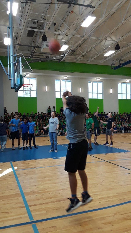 A+sixth+grader+takes+his+shot+as+his+fellow+classmates+cheer+him+on.