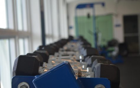Weights sit untouched in the school weight room as student athletes find alternatives at home.