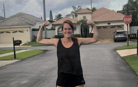 Mrs. Taylor, the cross country coach, flexes after running her 500th mile during quarantine.