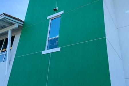 The newly painted exterior walls shine bright as an emerald.